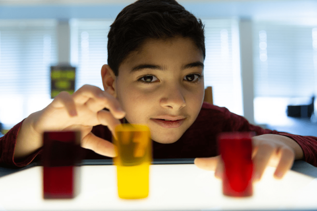 a young boy with CVI looks at colorful 3D shapes on a lightbox