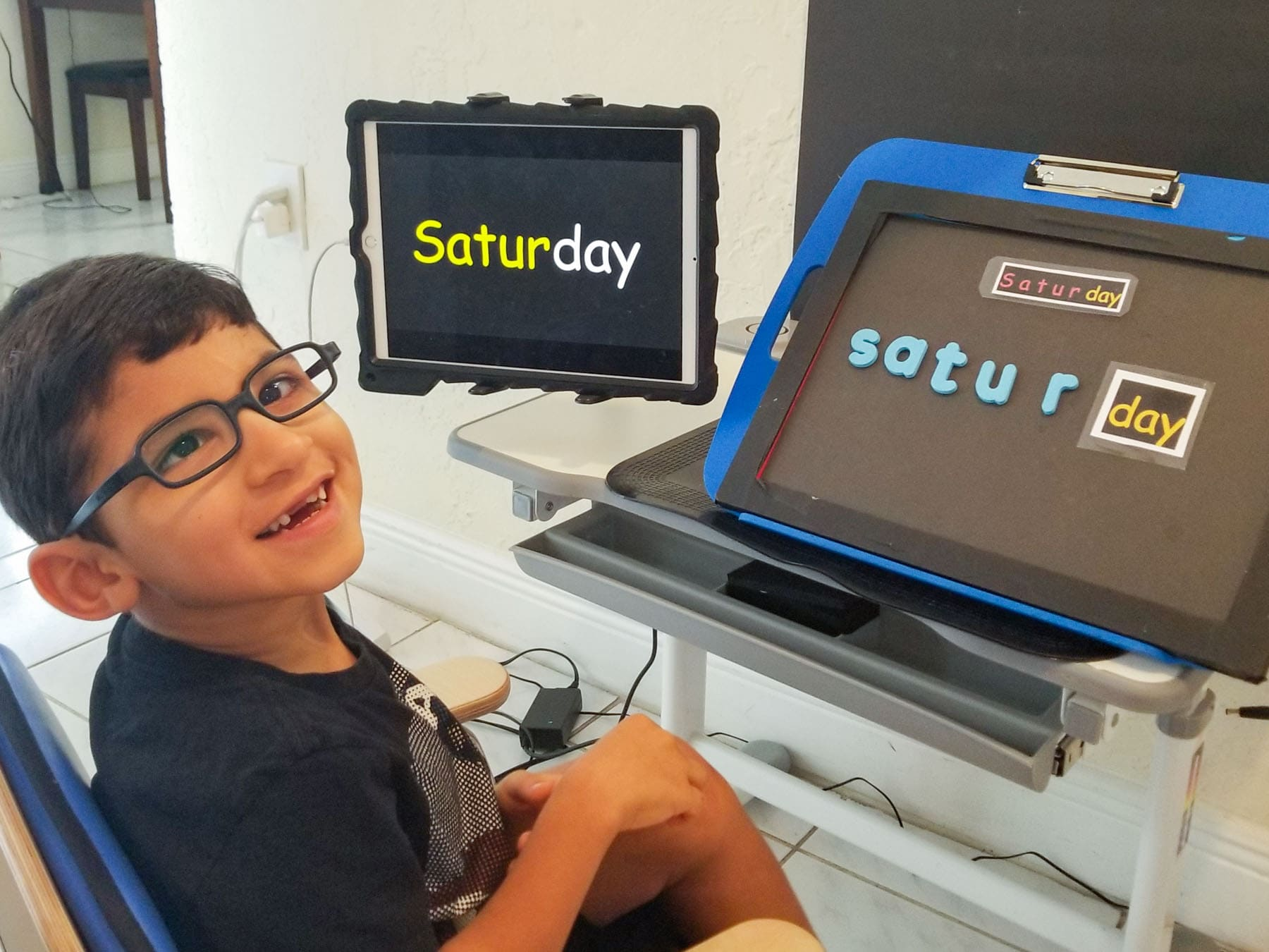 A young boy learning how to spell on an Ipad at a desk