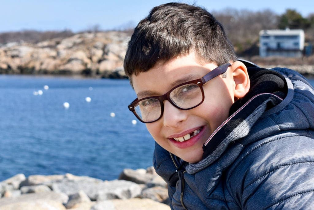A young boy wearing glasses and smiling in front of the ocean.