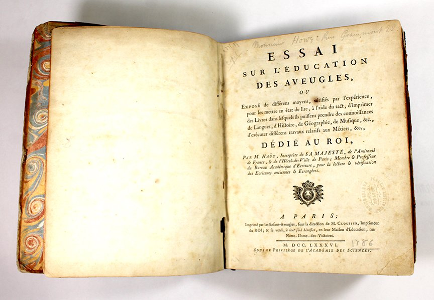 """Title page of """"An Essay on the Education of the Blind"""" with a dedication to the king of France. The pages show discoloring and foxing stains from age. A small portion of the marbled paper lining the front cover is exposed."""