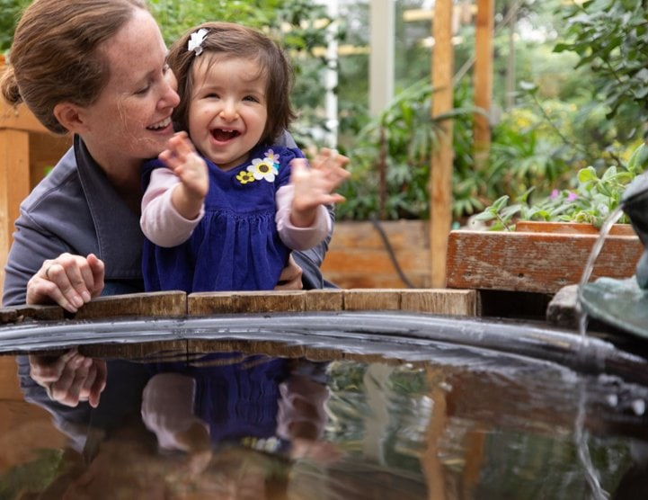 A little girl that is smiling in the arms of a woman by a fountain.