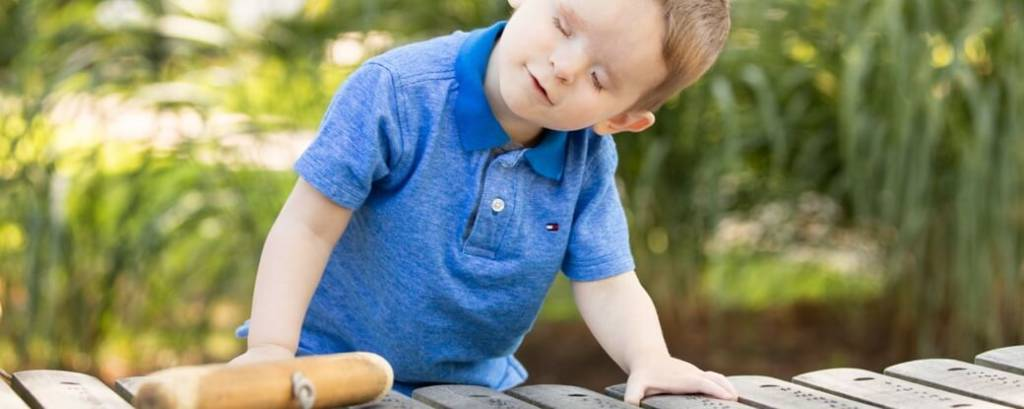 A young boy playing outside on a large xylophone