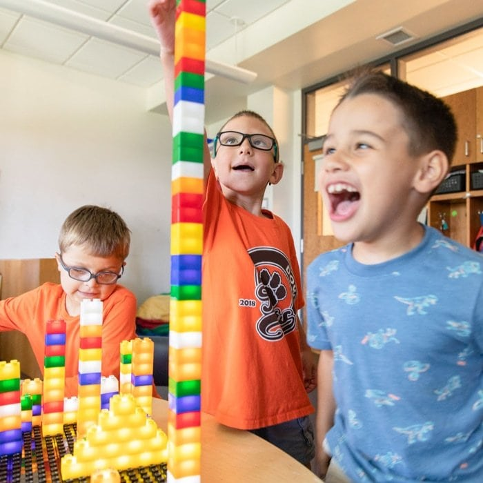 Three boys playing with building blocks in excitement