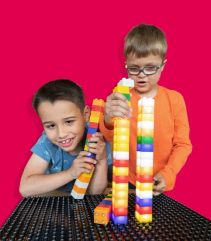 Two boys playing with building blocks with a red background