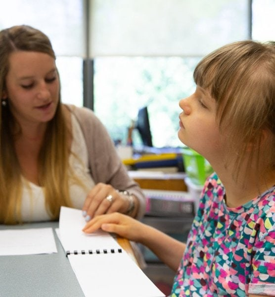 A visually impaired little girl using brailler with guidance from her teacher.