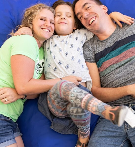 A family of three cuddled together on a blue mat, smiling during CVI Weekend event