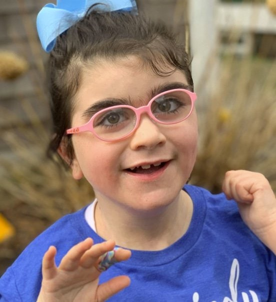 A young girl with pink glasses and a blue bow smiling.