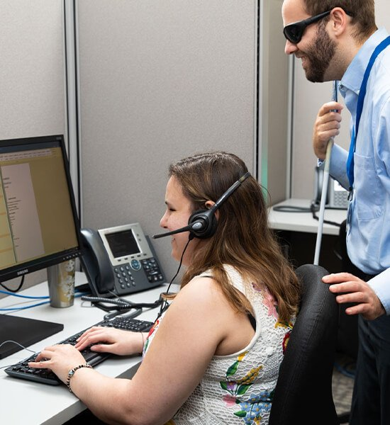 A girl with a headset on smiles at a computer screen, while a visually impaired man stands behind her and smiles as well.