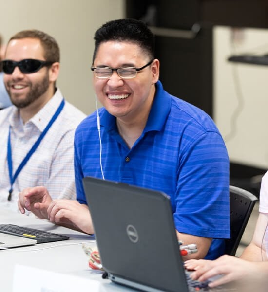 A student and instructor sit in a classroom, smiling while working on laptops
