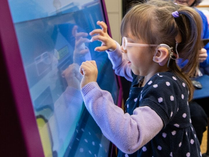 A little girl wearing pink glasses is placing both of her hands on a large screen.
