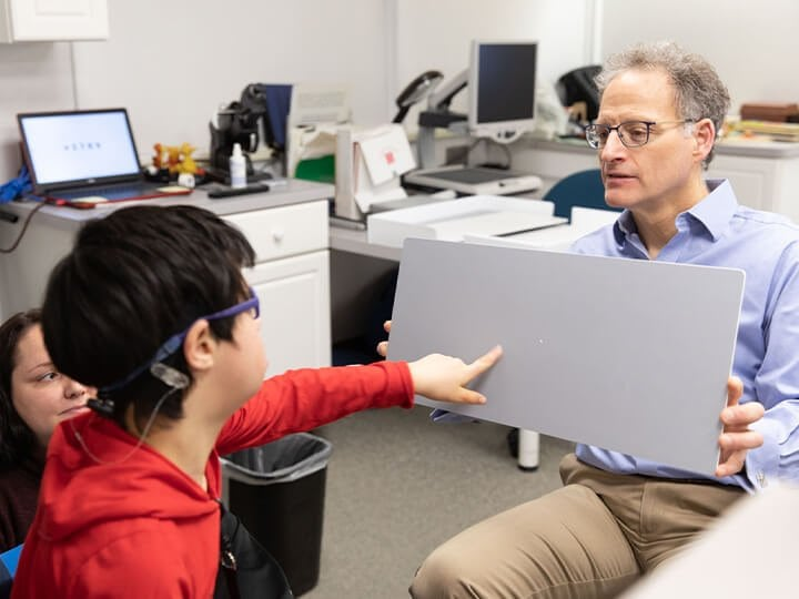 A boy with low vision points to a board that is being held by a man.
