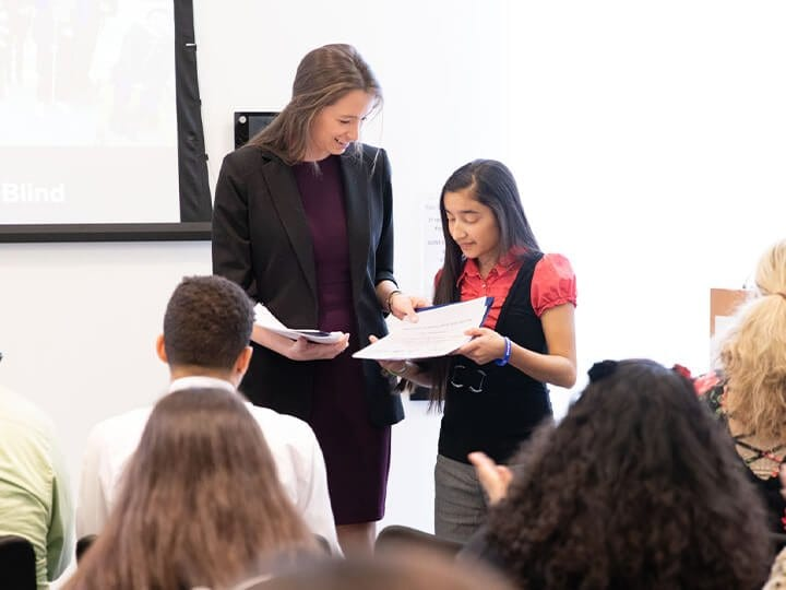 A visually impaired student standing in front of the class with her teacher to read aloud.