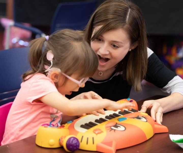 A young girl wearing pink glasses with a big smile on her face as she plays on a cat piano alongside her teacher.