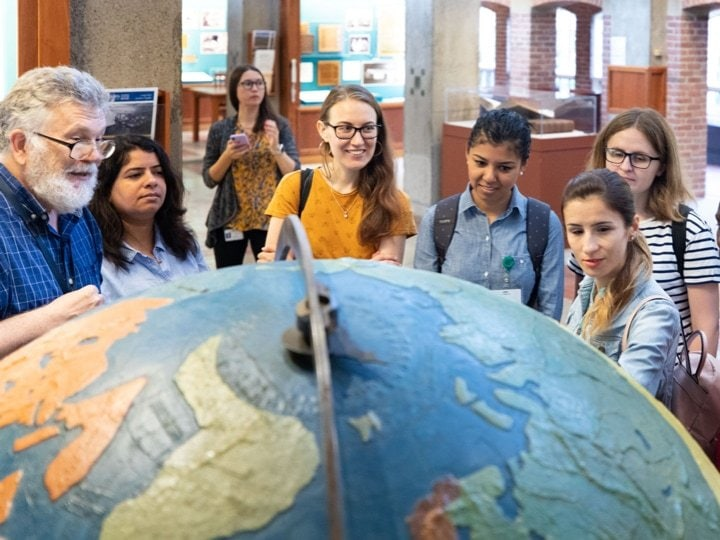 A group of students standing in a circle in front of a large globe