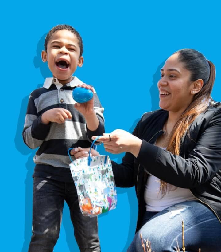 A Mother with her son doing an easter egg hunt with a blue background