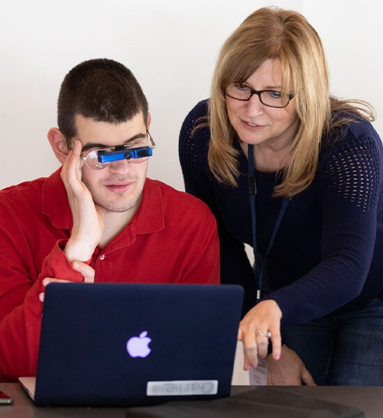 A visually impaired male being guided by his female teacher on a laptop at a table.