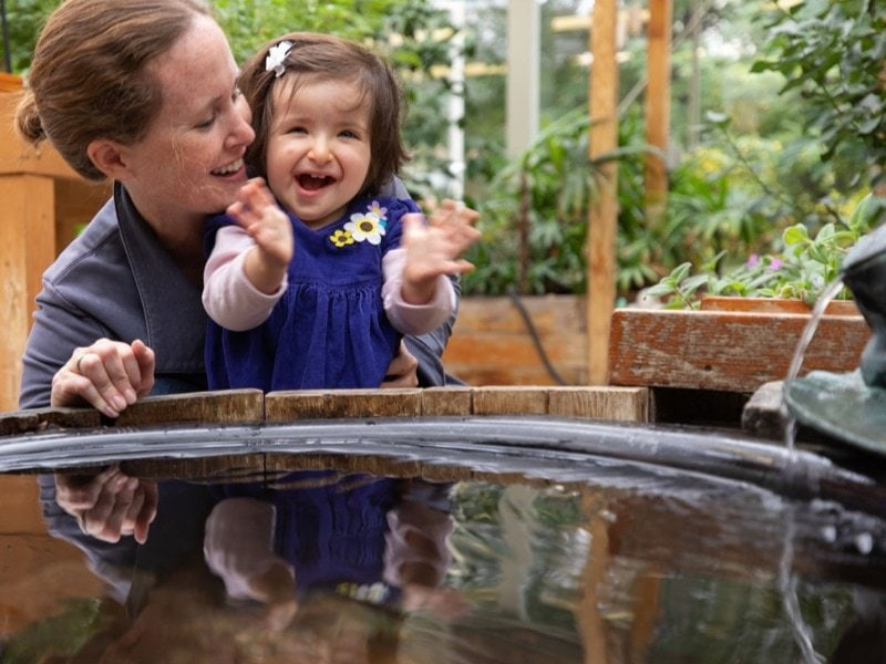 A young girl and her mother embracing with joy in front of a fountain.