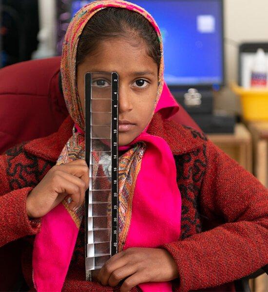 A little girl holding an eye tool.