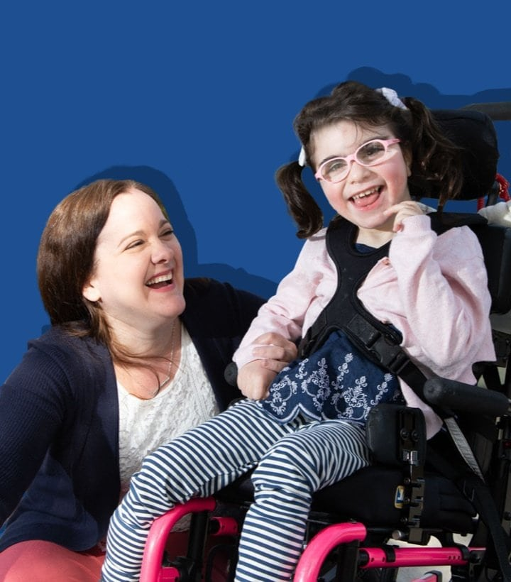 A young girl in a wheelchair smiling with a teacher on a blue background