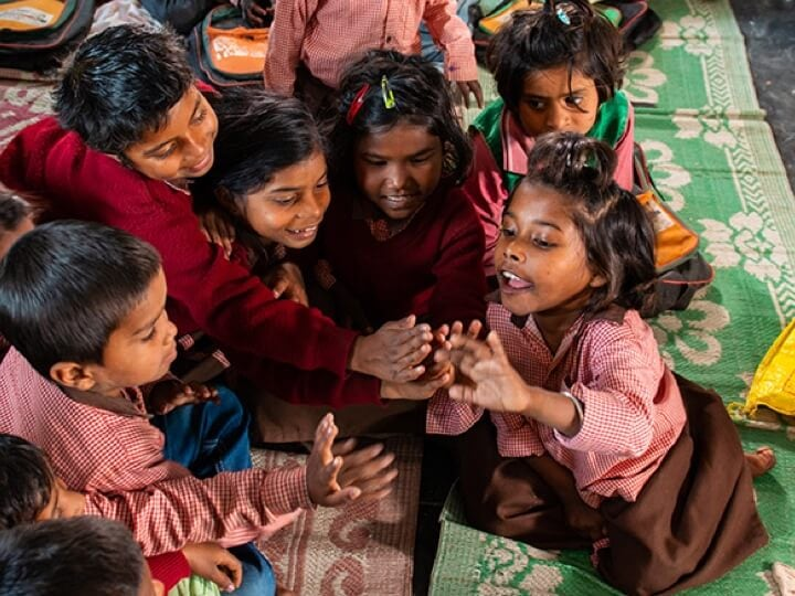 A group of children putting their hands together