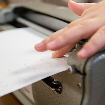 A young individual with their hands on braille.