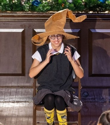 A female student with a Harry Potter costume on sitting in a chair