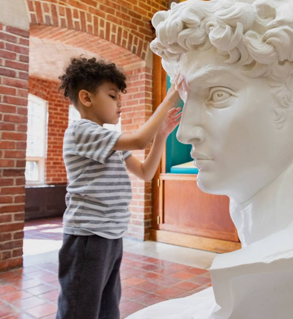 A young boy touching a large white statue in deep thought