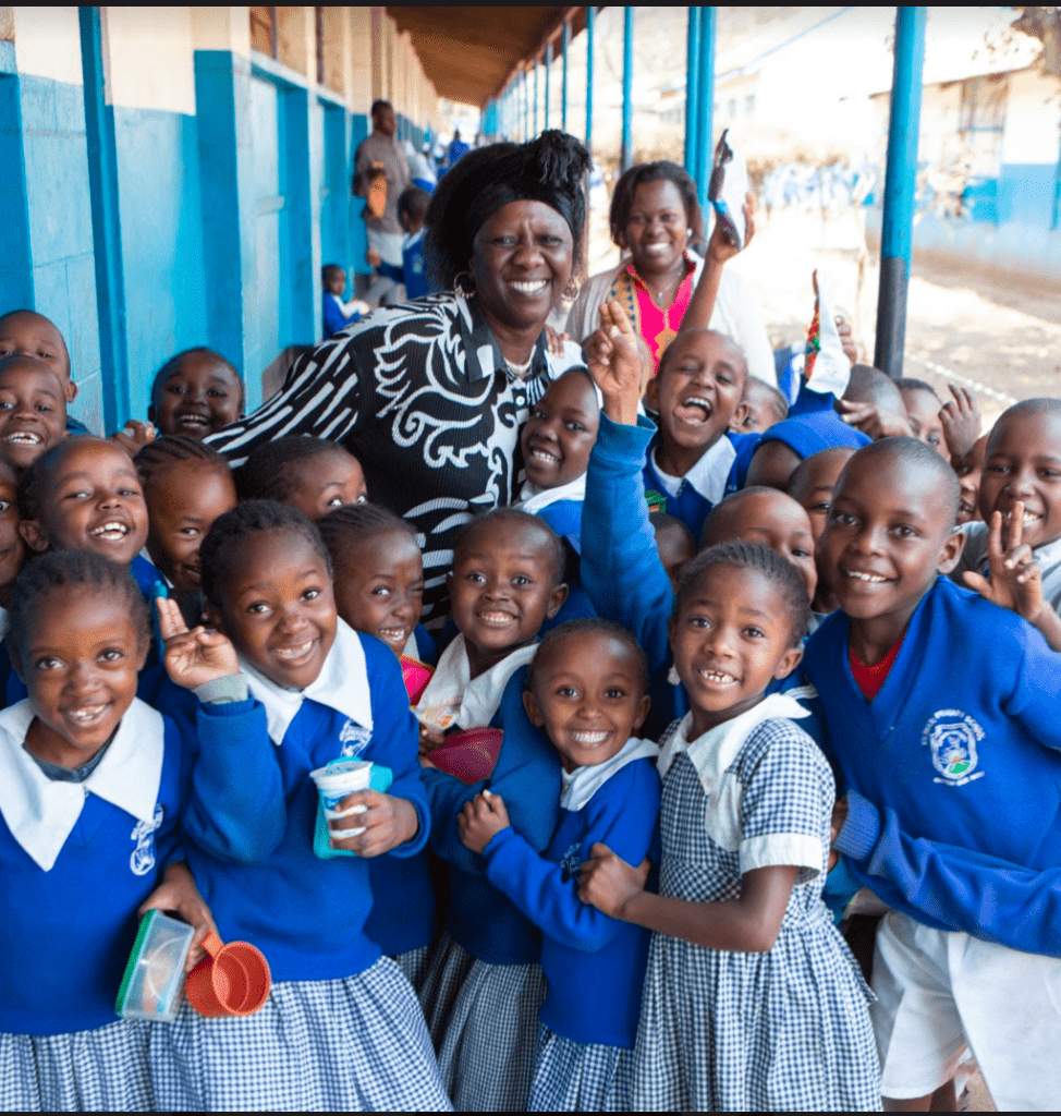 A large group of smiling children in matching school uniforms.