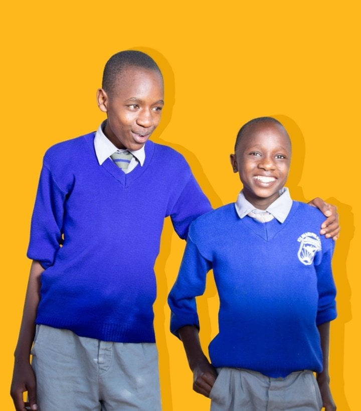 Two young Kenyan boys smiling together on a yellow background