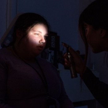 A light shining onto a small portion of a girls face, of which the rest remains entirely dark.
