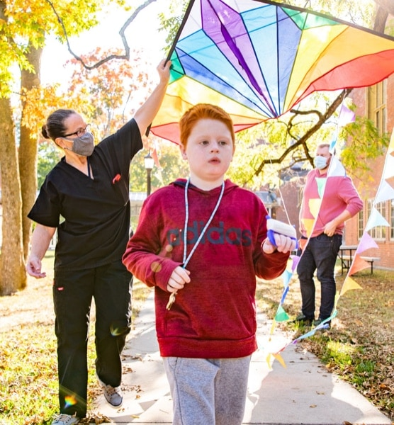 A visually impaired boy with bright red hair flying a colorful kite outside.