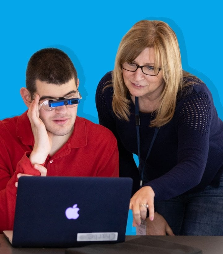 Student works with his teacher on a laptop.