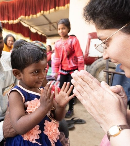A woman and a child greeting with their hands.