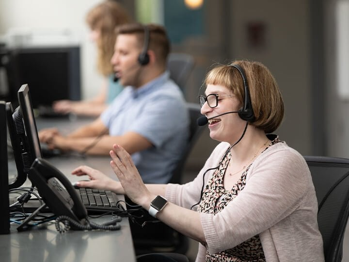 Woman with headset works at computer
