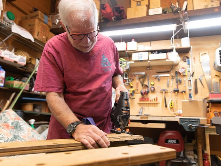 An older man that is focused while doing woodwork in a shop.
