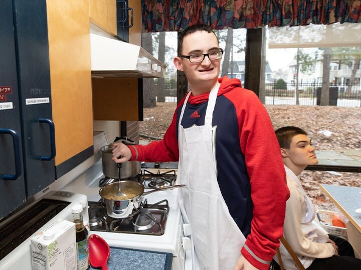 A visually impaired boy stirring food in a pot on the kitchen stove as he smiles.