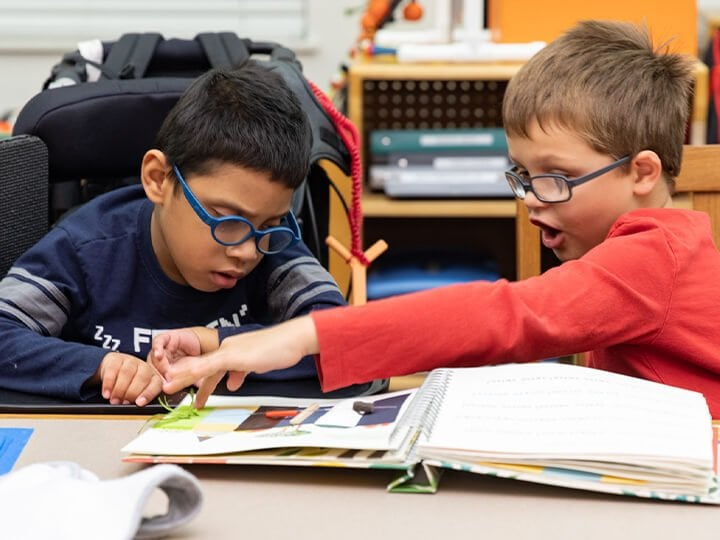Two visually impaired boys working together at a table and looking at a book.