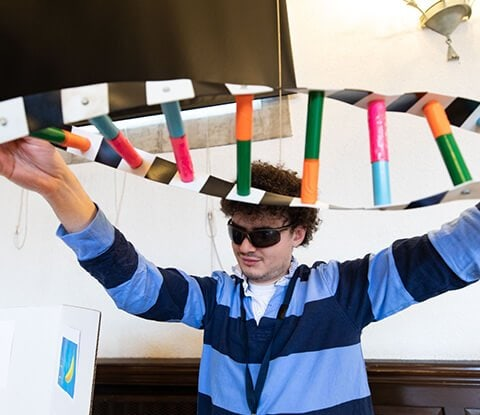 A male student holding up a colorful project