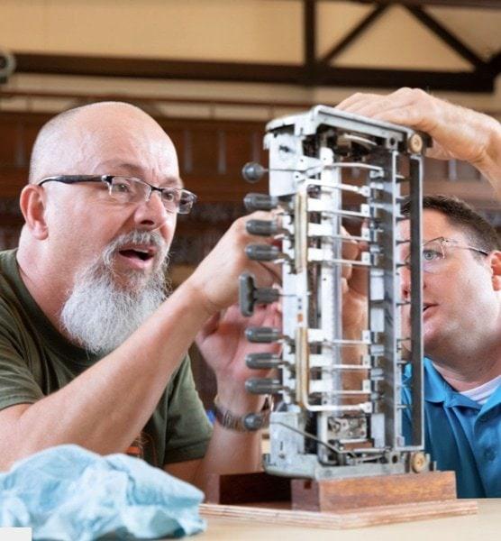 Two men working on a brailler machine.