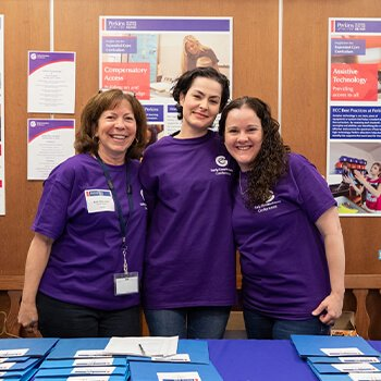 A group of three women in purple volunteer shirts