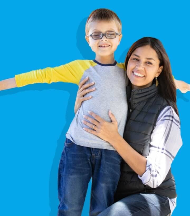 A woman and a boy smiling and hugging on a blue background