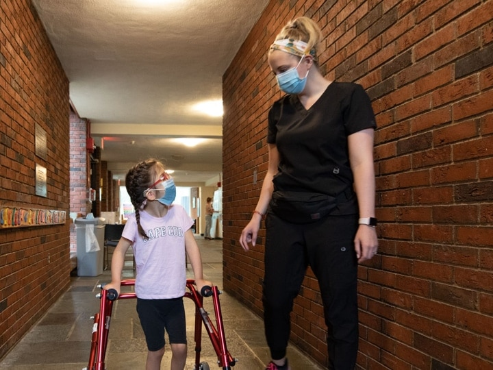 A young girl using her walker to walk alongside her teacher in a hallway.