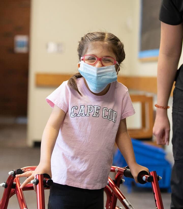 A young girl with a mask on using a walking device