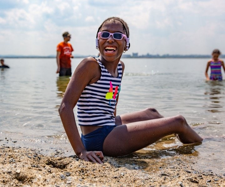 A girl with a big smile on her face sitting in the water on the beach.