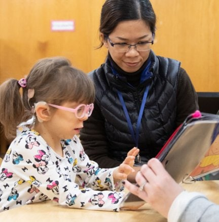 A little girl wearing pink glasses reading from a braille book alongside her teacher.