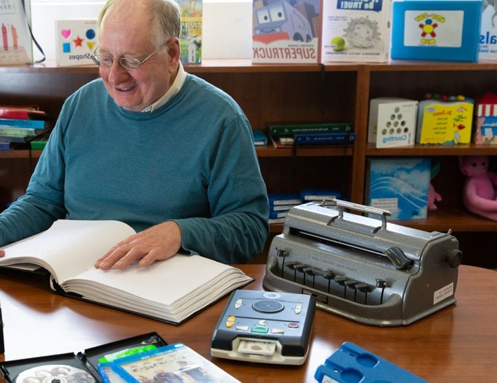 An old man with a big smile that is sitting at a table in the library with a braille book open.