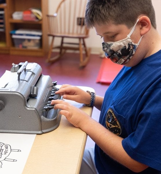 A young male student wearing a face mask while using brailler at a table.