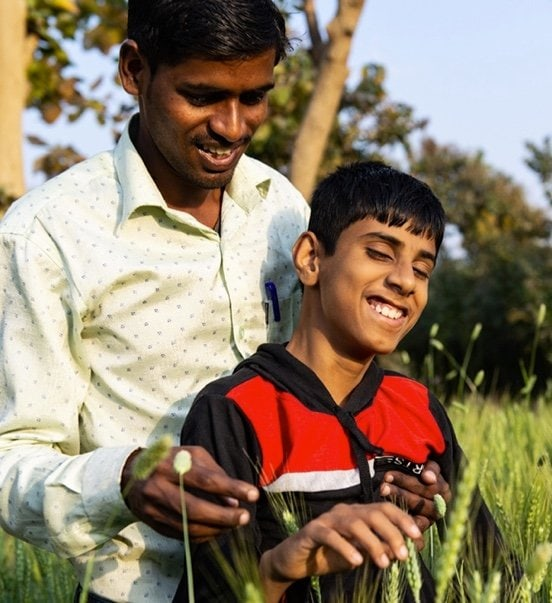 A man and a child smiling while touching plants
