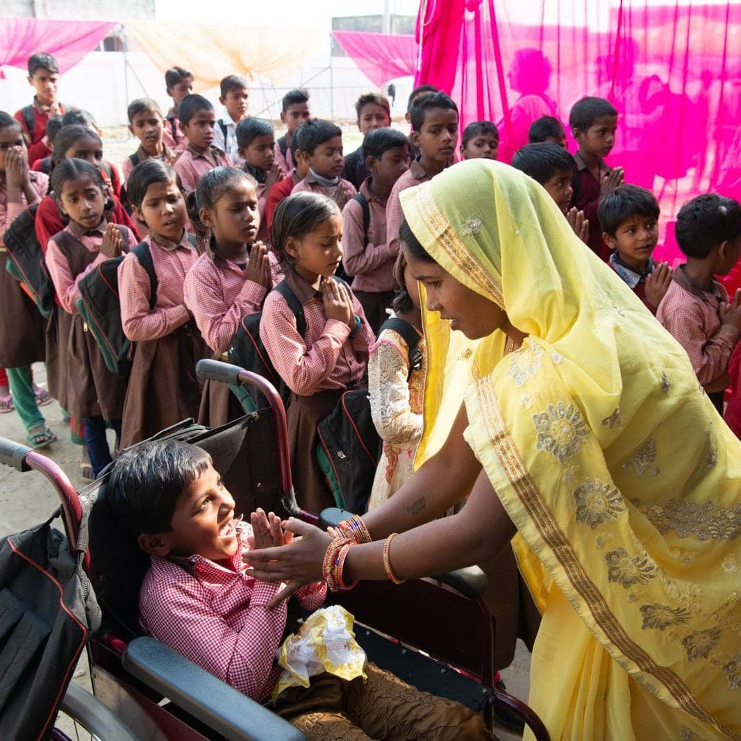 Woman dressed in a yellow Sari holds the hands of a smiling student sitting in a wheelchair