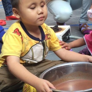 A young boy holding a bowl of liquid.
